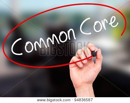 Man Hand writing Common Core with black marker on visual screen.
