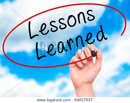 Man Hand writing Lessons Learned with black marker on visual screen.