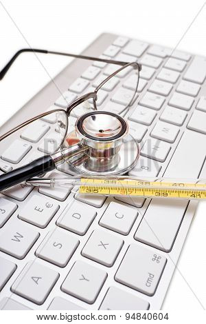 Stethoscope, Glasses, Medical Thermometer On Keyboard