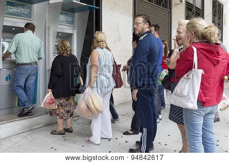 People Stand In A Queue To Use The Atms Of A Bank. Greece's Fraught Bailout Talks With Its Creditors