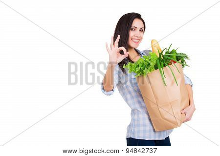 Happy young woman holding paper shopping bag with groceries. Smiling girl customer. Consumerism. Iso