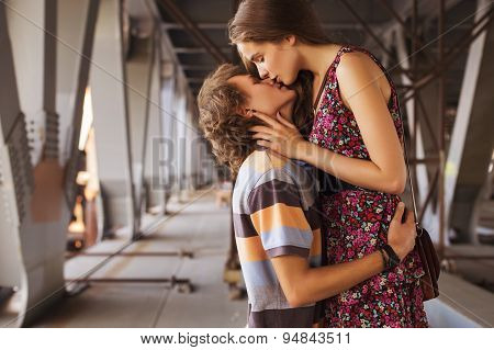 Young Couple Hugging In The Summer Daylight On A Bridge Construction In The City Outdoors. Copy Spac