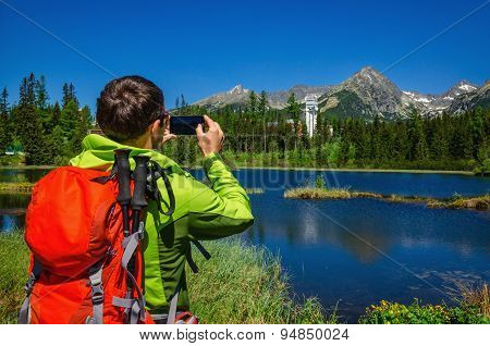 Young man takes picture of mountains and lake
