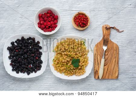 tasty summer fruits on a wooden table. raspberries, Blackberries, mulberry, currant, red and yellow