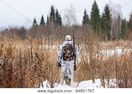 Hunter Walking On The Snowy Field