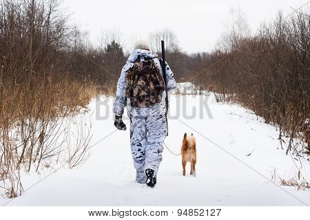 Hunter With Dog Walking On The Winter Road