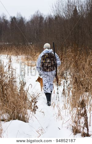 Hunter With Gun Shooting On The Snowy Field