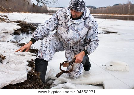 Hunter Setting A Leghold Trap For Beaver
