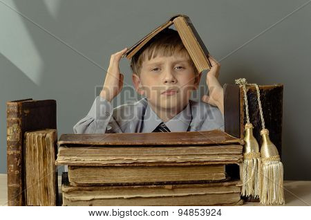 little boy carefully read old books