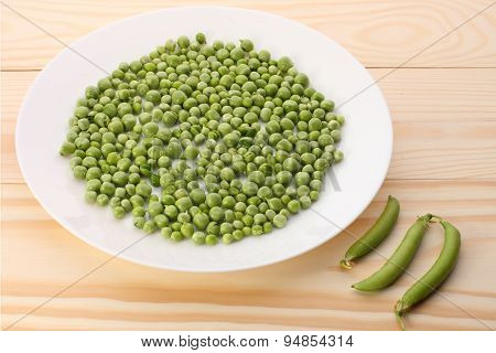 Green Peas  In White Plate And Pea Pods  On Wooden Table