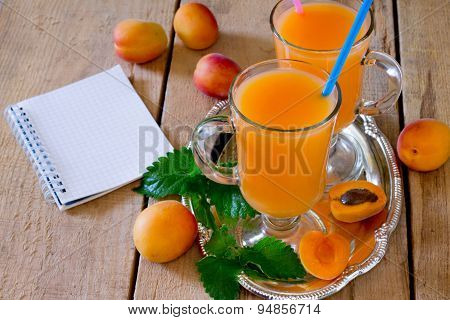 Fresh sweet apricot juice, notebook and fresh apricots