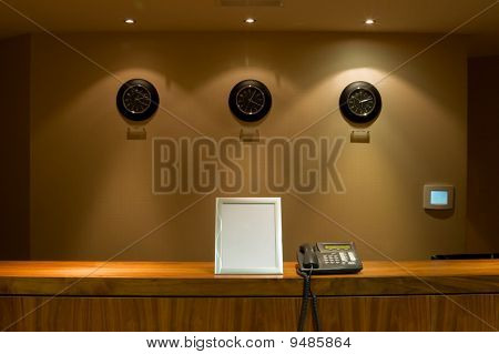 Hotel Reception Desk With Phone And Signboard
