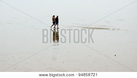 People walking on wet sandy beach