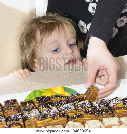 Little Boy Looking Curious At Cakes