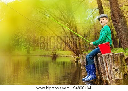 Boy fishing near beautiful pond with fishrod