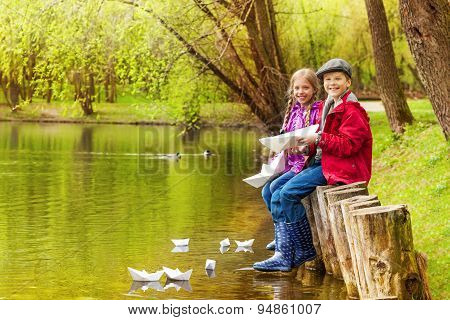 Sitting kids near the pond play with paper boats
