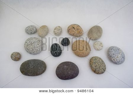 Smooth rocks from beach laid out with white background