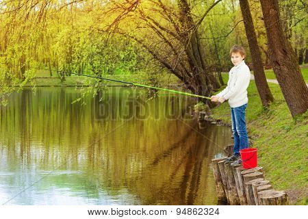 Boy standing and fishing near the pond