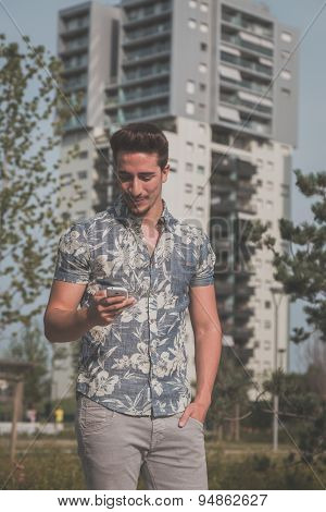 Young Handsome Man Texting In The Street
