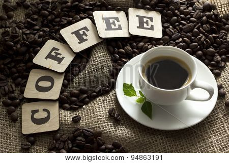 Cup of coffee and coffee beans letters