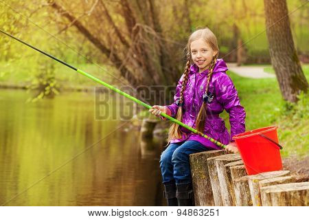 Portrait of smiling girl fishing near pond