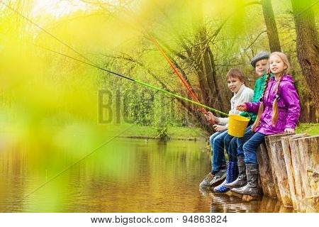 Kids sitting and fishing together near the pond