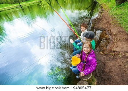 View from up of kids holding fishing tackles