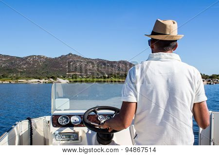 Man Driving A Boat Near The Coast