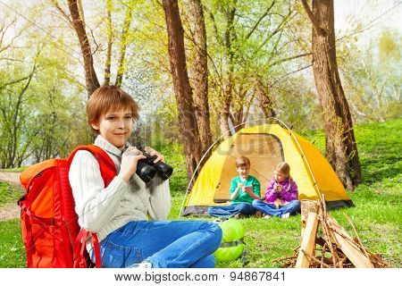 Boy with red backpack holding black binocular