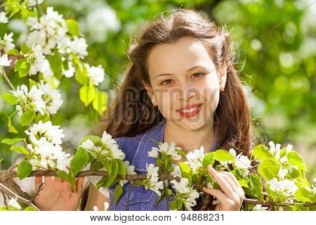 Attractive teenager girl with white pear flowers