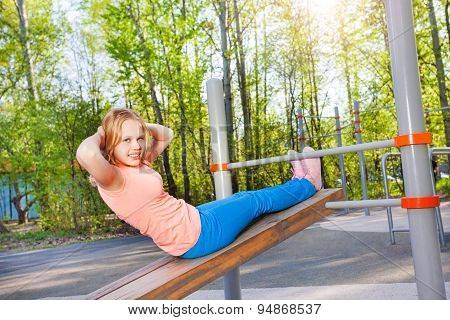 Blond girl curls up on board at the sports ground