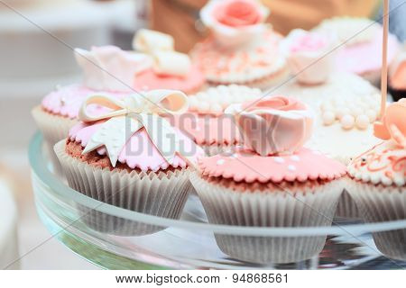 Tasty pink cakes on glass dish