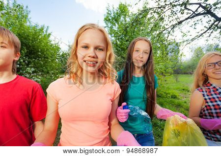 Close-up of teens with gloves and garbage bags