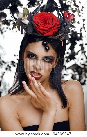 pretty brunette woman with rose jewelry, black and red, bright make up kike a vampire closeup