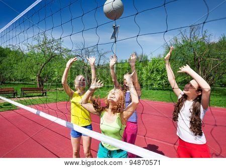 View through volleyball net of playing girls