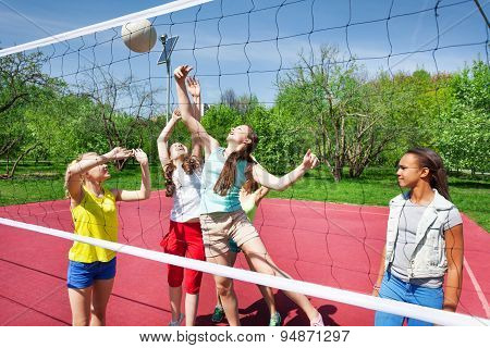 Teens are playing volleyball together on the court