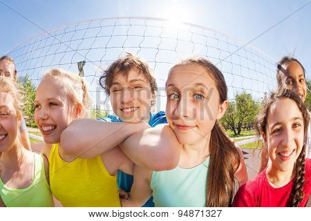 Happy teens in front of volleyball net, close-up