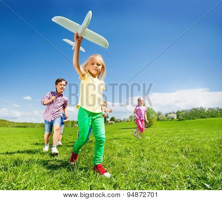 Close-up of girl with kids and white airplane toy