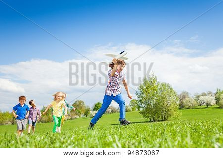 Boy with airplane toy running fast and other kids