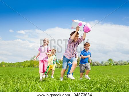 Happy boy holding rocket carton toy and kids run