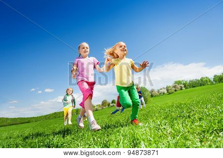 Happy girls and other kids running in green field