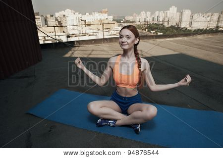 red haired lady meditates during workout