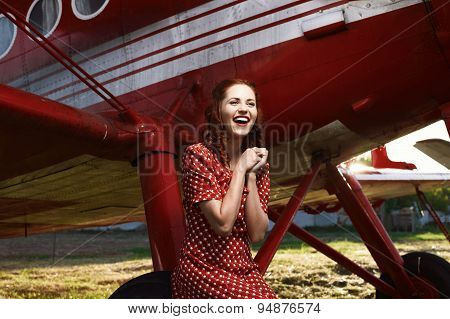 laughing pin-up female sitting on airplane wheel in red dress