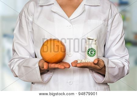 Young Doctor Holding Grapefruit And Bottle Of Pills With Vitamin
