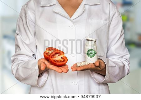 Young Doctor Holding Tomato And Bottle Of Pills With Vitamins An