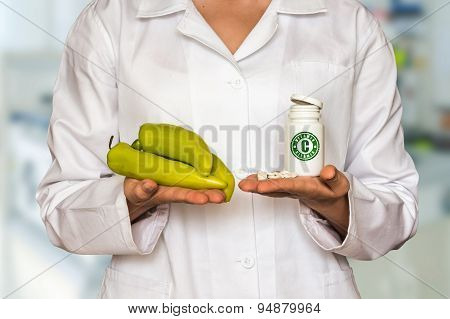 Young Doctor Holding Pepper And Bottle Of Pills With Vitamin C A