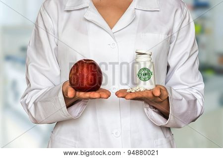 Young Doctor Holding Apple And Bottle Of Pills With Vitamins And