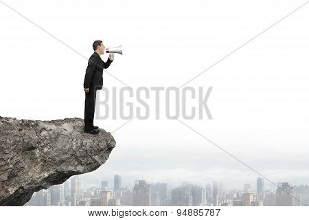 Businessman Using Speaker Yelling On Cliff With City Skyline