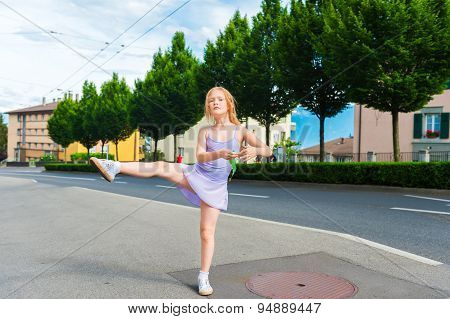 Outdoor portrait of a cute little girl of 7 years old, walking to dance school and dancing in the st