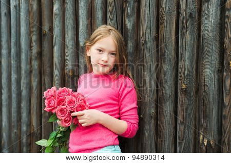 Outdoor portrait of a cute little girl against wooden wall, wearing bright pink pullover, holding bo